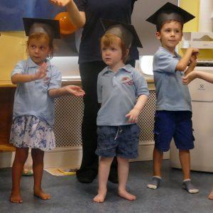 young children wearing paper graduation caps