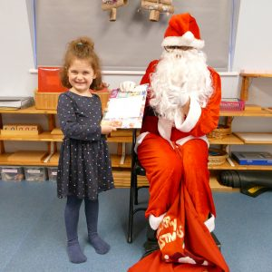small child receiving a gift from santa