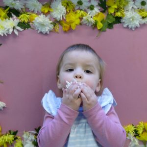 baby kissing a flower