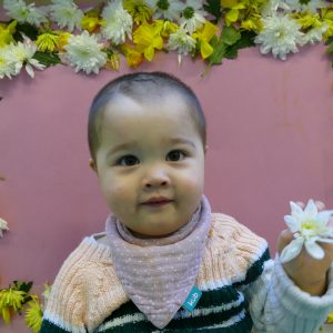 baby holding a flower