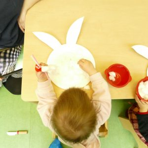 young child making bunny out of paper plates and cotton wool